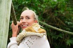 Schließen Sie herauf Schuss wenn das junge blonde Mädchen, das in einer gehenden Holzbrücke sitzt Stockbild