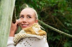 Schließen Sie herauf Schuss wenn das junge blonde Mädchen, das in einer gehenden Holzbrücke sitzt Stockfoto