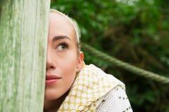 Schließen Sie herauf Schuss wenn das junge blonde Mädchen, das in einer gehenden Holzbrücke sitzt Stockbilder