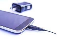 Schließen Sie herauf schwarzen Smartphone und USB-Kabel auf weißem Hintergrund Lizenzfreie Stockbilder