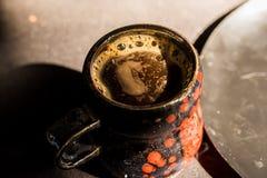 Schließen Sie herauf schwarzen und roten Becher der Weinlese mit Kaffee Lizenzfreies Stockfoto