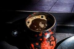 Schließen Sie herauf schwarzen und roten Becher der Weinlese mit Kaffee Lizenzfreie Stockfotografie