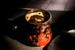 Schließen Sie herauf schwarzen und roten Becher der Weinlese mit Kaffee Stockfoto