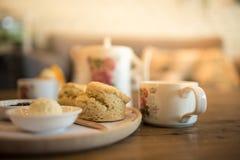 Schließen Sie herauf Scones mit Butter und Tee auf dem Tisch lizenzfreie stockfotos