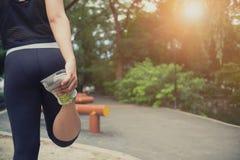 Schließen Sie herauf Seitenansicht des Eignungsfrauenläufers, der Beine ausdehnt Stockfoto