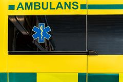 Schließen Sie herauf Seitenansicht eines gelben und grünen schwedischen Sanitätswagens lizenzfreies stockfoto