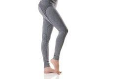 Schließen Sie herauf sexy Seitenansicht von den Frauenbeinen, welche die Muskeln des Fußes in der thermischen Unterwäsche des Gra Stockfotografie