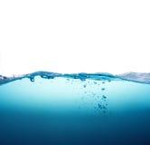 Schließen Sie herauf Spritzen des blauen Wassers mit Blasen auf weißem Hintergrund Stockfoto