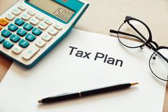 Schließen Sie herauf Steuerplanungswort auf Papier mit Taschenrechner-, Stift- und Augenglasplatz auf dem Holztisch Stockbilder