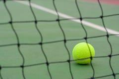 Schließen Sie herauf Tennisball und verwischen Sie Netz auf Gerichtshintergrund lizenzfreies stockbild