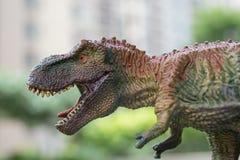 Schließen Sie herauf Tyrannosaurusspielwaren vorangehen mit Gebäude an der Rückseite Lizenzfreies Stockfoto