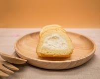 Schließen Sie herauf Vanillekuchenrolle im hölzernen Teller auf Holztisch, orange Hintergrund Lizenzfreie Stockfotos