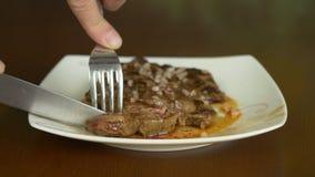 Schließen Sie herauf verschlossenen Schuss des Steaks Hände mit Messer und Gabel nehmen vom Fleischsteak von der Platte teil stock footage