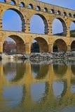 Schließen Sie herauf vertikales Bild des Niveaus mit drei Bögen von Pont DU Gard mit klarer Reflexion auf Gardon-Fluss Stockfotos
