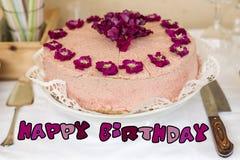 Schließen Sie herauf violette Blumen des Sahnekuchens auf alles Gute zum Geburtstag des Spitzentafelsilbers und des bunten Textes Lizenzfreie Stockfotografie