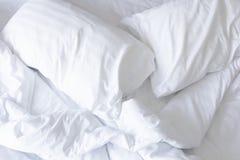 Schließen Sie herauf weiße Bettwäscheblätter und -kissen lizenzfreies stockbild