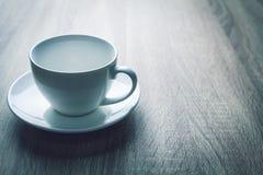 Schließen Sie herauf weiße Kaffeetasse auf schwarzer hölzerner Tabelle nahe Fenster stockfotografie