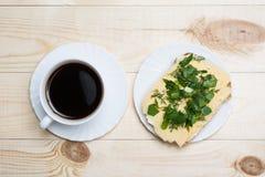 Schließen Sie herauf weiße Kaffeetasse und Sandwich auf Holztisch stockfoto