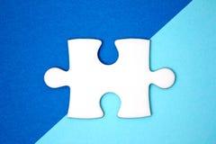 Schließen Sie herauf weißes Puzzlespielstück über einem Geometrieblauhintergrund lizenzfreie stockfotografie
