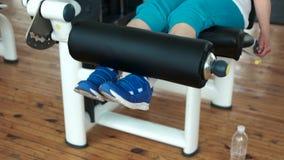 Schließen Sie herauf weibliche Beine auf Gewichthebenmaschine stock footage