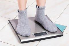 Schließen Sie herauf weibliche Füße auf digitaler Gewichtungsskala lizenzfreies stockbild
