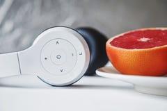 Schließen Sie herauf Zusammensetzung des weißen unbedeutenden Kopfhörers und Hälfte von fre lizenzfreie stockfotos