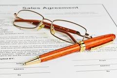 Schließen Sie mit den Gläsern und hölzernem Stift Vertrag ab, die bereit sind unterzeichnet zu werden Stockfotografie
