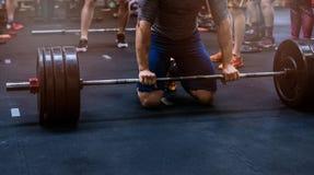 Schließen Sie oben auf dem muskulösen Mann, der zum Gewichtheben sich vorbereitet stockfotos