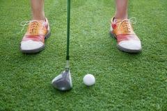 Schließen Sie oben auf den Füßen und Golfclub, die fertig wird, einen Golfball zu schlagen Stockfoto