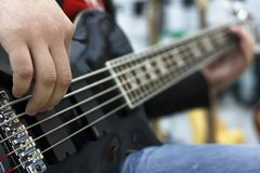 Schließen Sie oben auf den Fingern des Musikers Bass-Gitarre auf dem Stadium spielend Stockbild