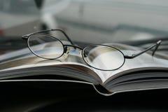 Schließen Sie oben auf den Gläsern und der Zeitschrift Stockfotos