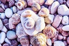 Schließen Sie oben auf den rosa und grauen gestreiften Steinen der verschiedenen Größen mit den Strahlen der Sonne, die auf sie f stockbilder