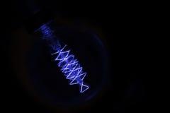 Schließen Sie oben auf der Blaulichtbirne, die in Dunkelheit glüht Stockbild