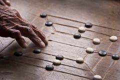 Schließen Sie oben auf der Hand eines alten Mannes, der Mühlespiel spielt Lizenzfreie Stockbilder
