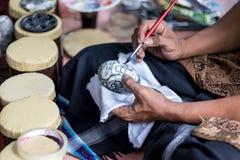 Schließen Sie oben auf der Hand eines Künstlers mit einem Pinsel und Buddha auf Ei malen Tropische Bali-Insel, Indonesien Stockbilder