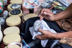 Schließen Sie oben auf der Hand eines Künstlers mit einem Pinsel und Buddha auf Ei malen Tropische Bali-Insel, Indonesien Lizenzfreie Stockfotos