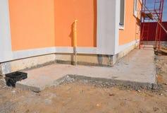 Schließen Sie oben auf der imprägniernden Grundmauer, Entwässerung, Gasrohr, bunte Fassade Lizenzfreie Stockbilder