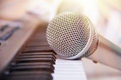 Schließen Sie oben auf einem Mikrofon während der Aufnahmesitzung mit einem Sänger, Klavier im Hintergrund, Musikstudio, helle Le Stockbilder