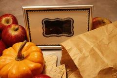 Schließen Sie oben auf einem Miniaturkürbis und einem knusprigen Brot, die vor einem gestalteten leeren Tafelzeichen liegen stockbilder