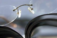 Schließen Sie oben auf einem Paar der Gläser und der Zeitschrift Lizenzfreies Stockfoto