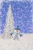 Schließen Sie oben auf einem Schneemann und gefrorenen einem Weihnachtsbaum, blaue bokeh Lichter im Hintergrund stockbild