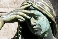 Schließen Sie oben auf einer Statue einer betenden Frau Stockfoto