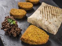 Schließen Sie oben auf französischen Tacos mit Nuggets, Cordon bleu und Rindfleisch auf Schiefer Stockbilder
