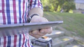 Schließen Sie oben auf Mann ` s Händen, die Tablette grasen Schieberschuß stock video