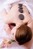 Schließen Sie oben auf schöner junger blonder Dame, die den Spaß hat, der Entspannung während der Steintherapiemassage auf Betthi Stockfoto