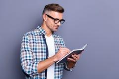 Schließen Sie oben das hübsche Foto er er sein Kerl, Hand, diearme das Notizbuch halten, das Anmerkungen macht, Autor Inspiration stockfoto