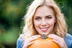 Schließen Sie oben, die schöne junge blonde Frau, die orange Kürbis hält Stockbild