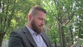 Schließen Sie oben, Geschäftsmanngrasentablette outdoor steadicam Schuss stock video footage