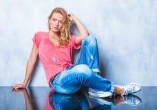 Schließen Sie oben mit dem blonden Mädchen, das auf dem Boden sitzt und leanin aufwirft Lizenzfreie Stockfotografie