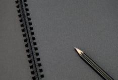 Schließen Sie oben am schwarzen Bleistift auf leerem schwarzem Notizbuch, Spott oben für das Addieren Ihres Inhalts Lizenzfreie Stockfotografie